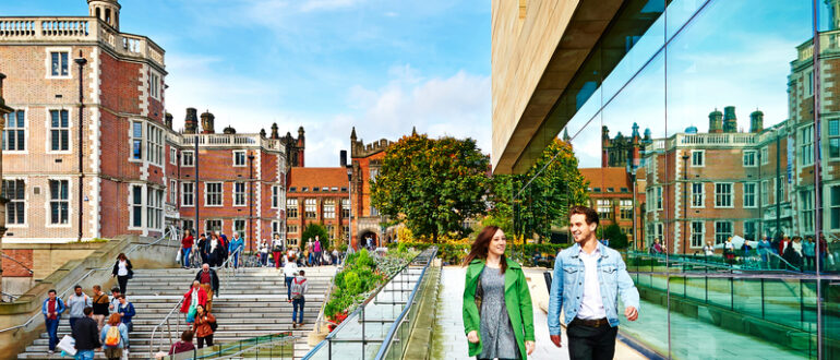 A bustling Newcastle University Campus. A mix of attractive old red brick buildings and modern glass buildings.
